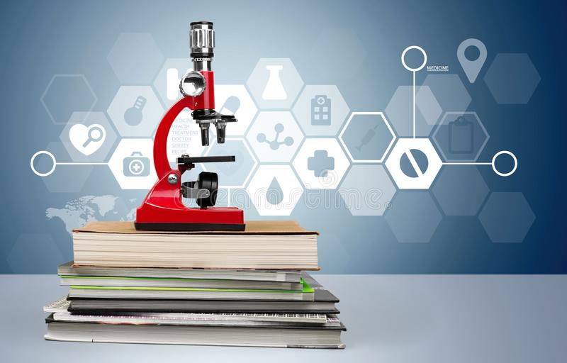 Microscópio no livro da pilha foto de stock