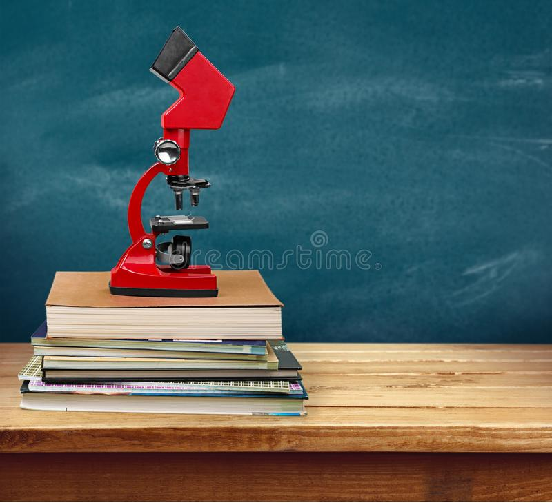Microscópio nos livros imagens de stock royalty free