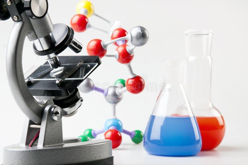 Microscópio, tubos de ensaio e átomos imagem de stock