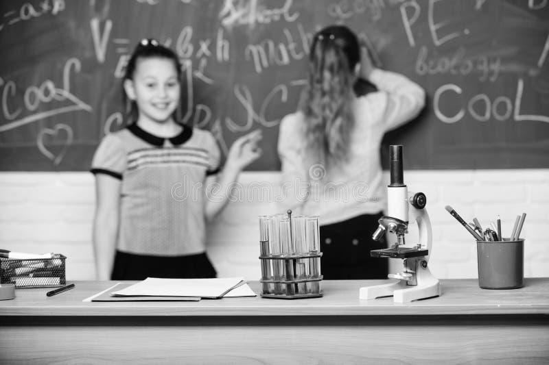 Microscoop en reageerbuizen op lijst chemische reacties Maak het bestuderen van chemie het interesseren Leerling bij bord  stock fotografie