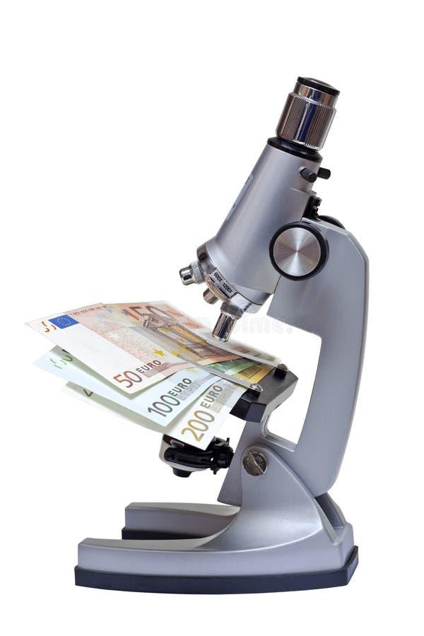 Microscoop met euro bankbiljet op wit royalty-vrije stock afbeeldingen