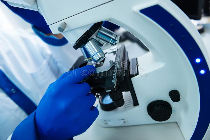 Scientists using a microscope in the lab. Microscope. Researcher wearing a uniform and medical gloves and sitting at a modern advanced cutting-edge microscope stock images
