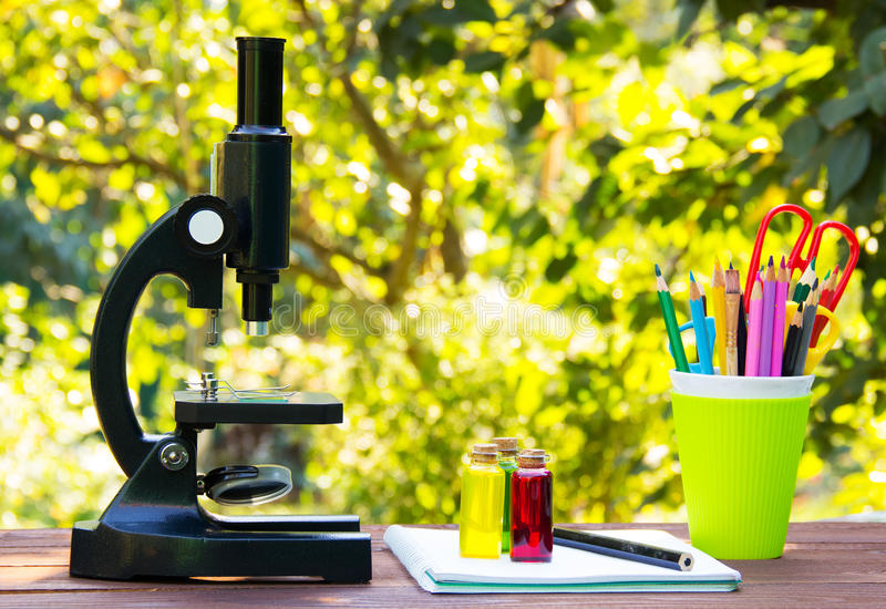 Microscope and stationery on wooden table. Glass flasks with colored liquids Natural green blur background. School concept. royalty free stock images