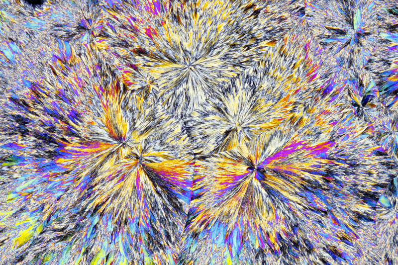 Microscopic view of citric acid crystals in polarized light. Microscopic view of citric acid crystals. Polarized light, crossed polarizers royalty free stock photos