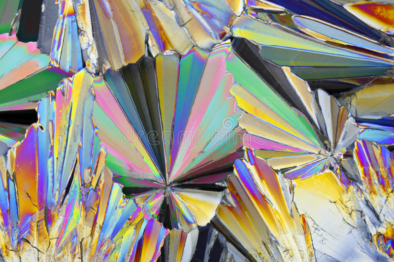 Microscopic view of sucrose crystals in polarized light. Microscopic view of colorful sucrose crystals. Recrystallized table sugar. Polarized light, crossed stock photography