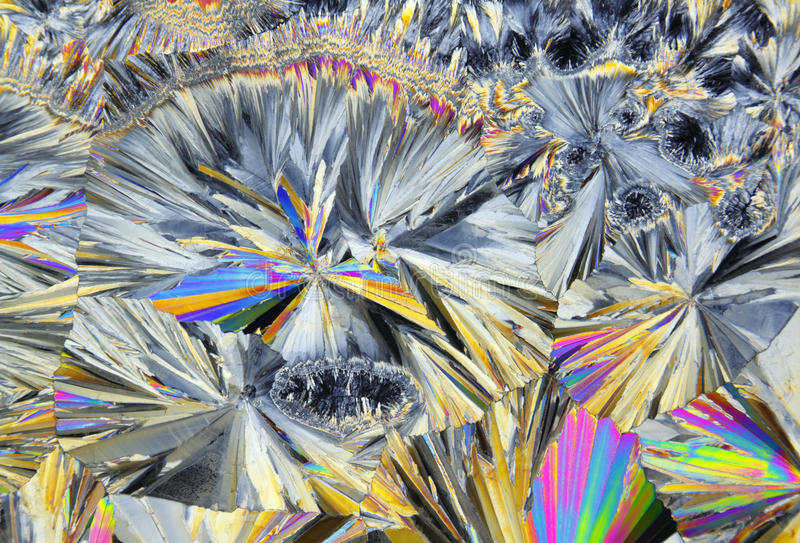 Microscopic view of sucrose crystals in polarized light. Microscopic view of colorful sucrose crystals. Recrystallized table sugar. Polarized light, crossed royalty free stock photography