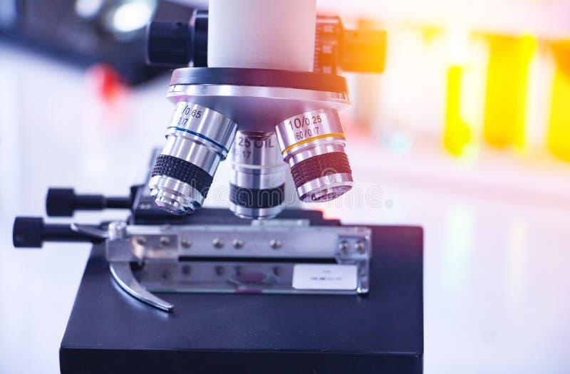 Microscopio alto vicino con la provetta variopinta fotografia stock