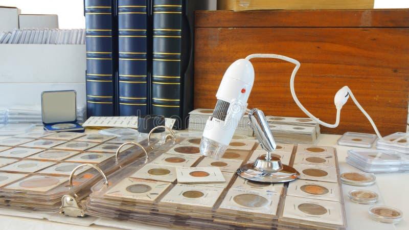 Microscopio de Digitaces en álbum con las monedas de los países diferentes imagenes de archivo