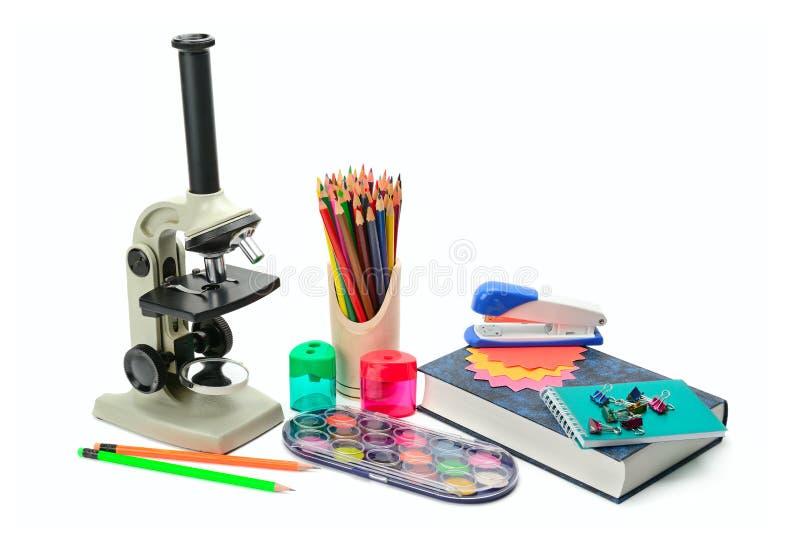Microscopio del laboratorio, manuale e l'altro isolat dei rifornimenti di scuola fotografia stock