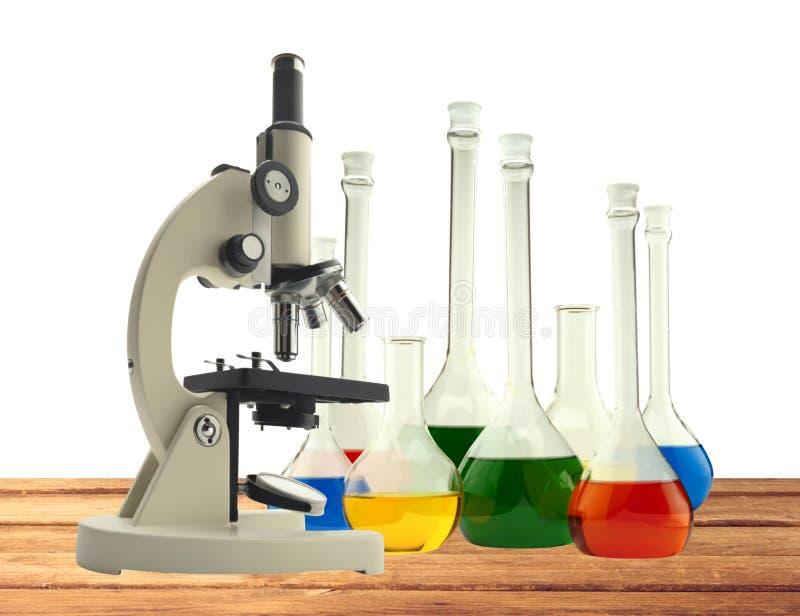 Microscopio del metallo del laboratorio e provette con liquido su di legno immagini stock libere da diritti