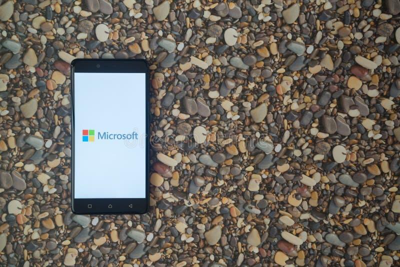Microsoft-embleem op smartphone op achtergrond van kleine stenen stock fotografie