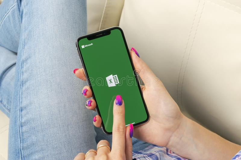 Microsoft Exel application icon on Apple iPhone X screen close-up in woman hands. Microsoft office Exel app icon. Microsoft offic royalty free stock image