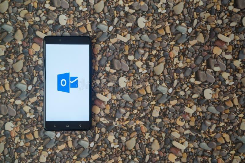 Microsoft-het embleem van bureauvooruitzichten op smartphone op achtergrond van kleine stenen royalty-vrije stock afbeeldingen