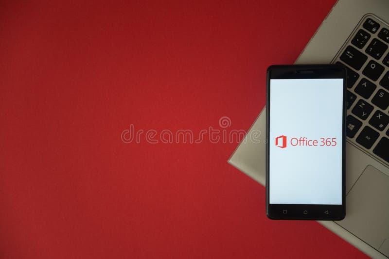 Microsoft Office 365 embleem op het smartphonescherm op laptop toetsenbord wordt geplaatst dat stock foto's