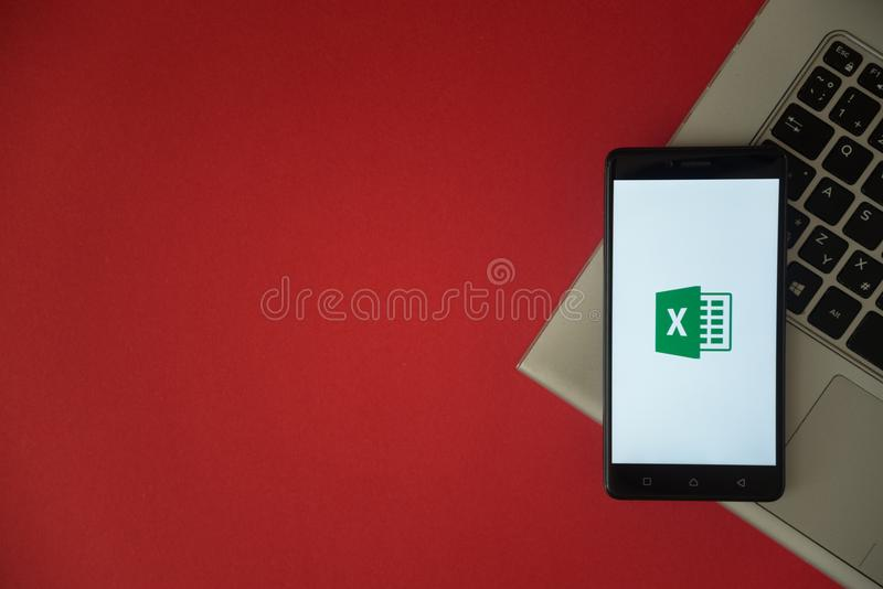 Microsoft office excel logo on smartphone screen placed on laptop keyboard. stock photography