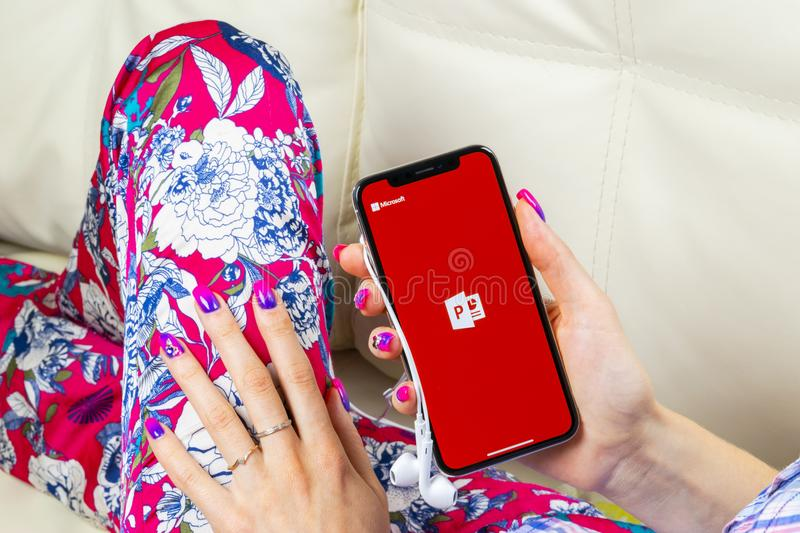 Microsoft office Powerpoint application icon on Apple iPhone X screen close-up in woman hands. PowerPoint app icon. Microsoft Powe. Sankt-Petersburg, Russia royalty free stock photography