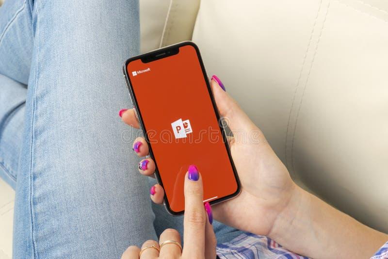 Microsoft Office Powerpoint podaniowa ikona na Jabłczany X iPhone parawanowym zakończeniu w kobiet rękach PowerPoint app ikona Mi zdjęcia stock