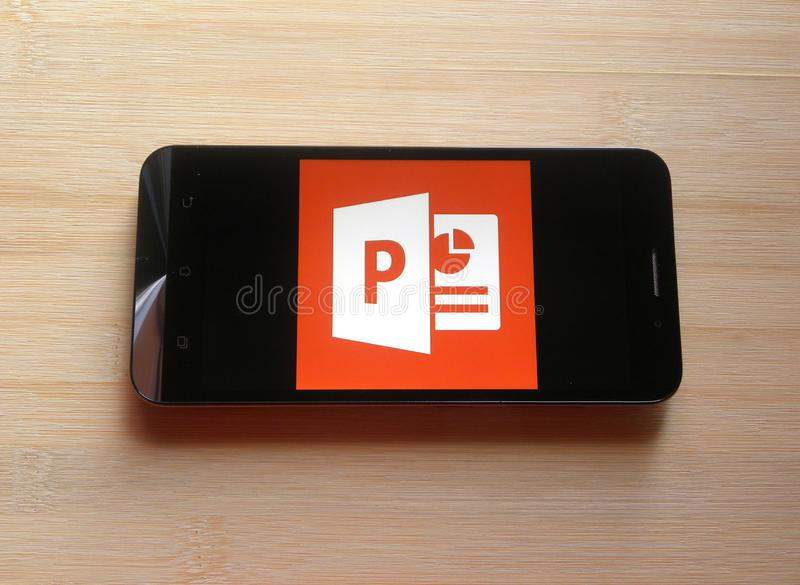 Microsoft PowerPoint app. On smartphone kept on wooden table royalty free stock photo