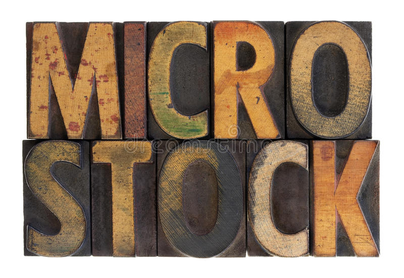 Microstock - vintage wood letterpress type. The word microstock in vintage wood block type, stained by color ink, isolated on white stock photo