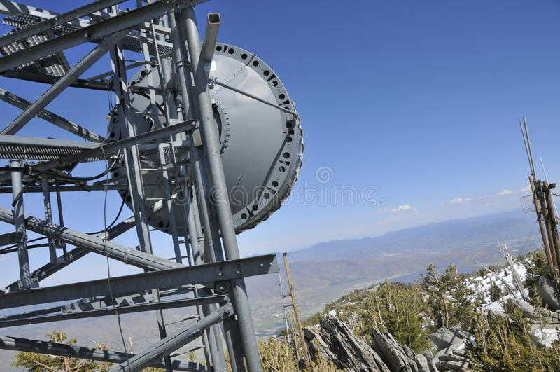 Microwave Antenna on Mtn. Peak. Remote Microwave Antenna on Top of Mountain Peak with Telecommunication Towers Overlooking Carson Valley, Nevada stock photo