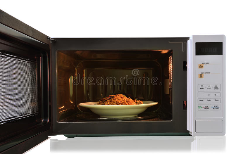 The microwave oven is warm fried noodles. royalty free stock images
