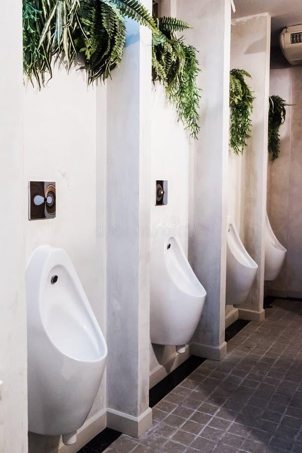 Mictório branco no toalete público dos homens com a telha preta da parede fotografia de stock