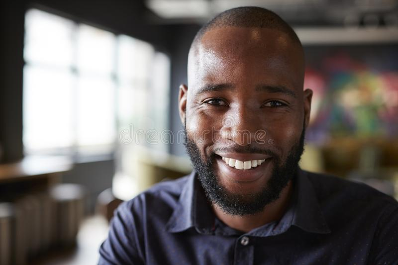 Mid adult black male creative sitting in an office dining area, head and shoulders close up royalty free stock photo