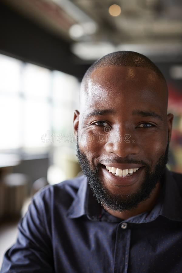 Mid adult black male creative sitting in an office social area, head and shoulders close up, vertical, crop stock image