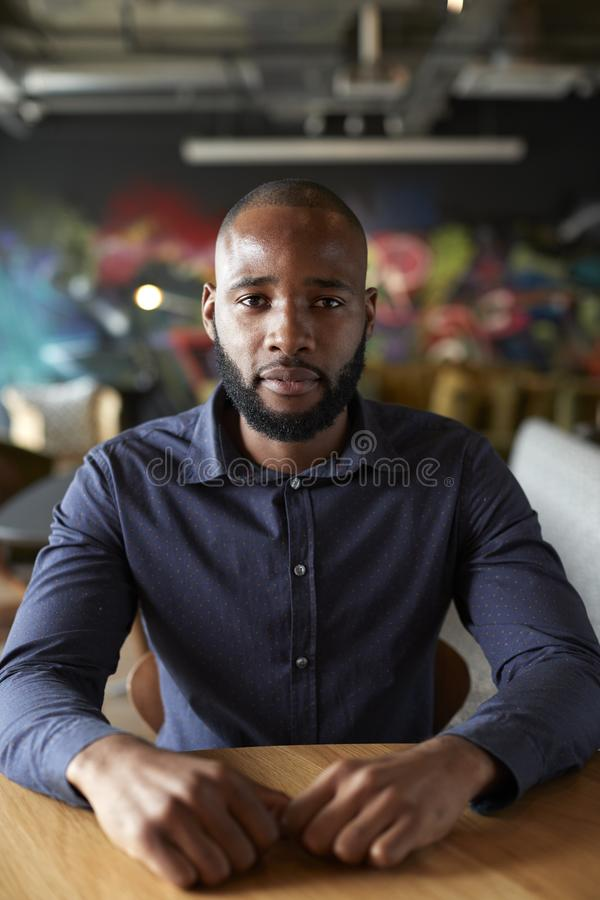 Mid adult black male creative sitting at a table in an office cafe looking to camera, close up stock images