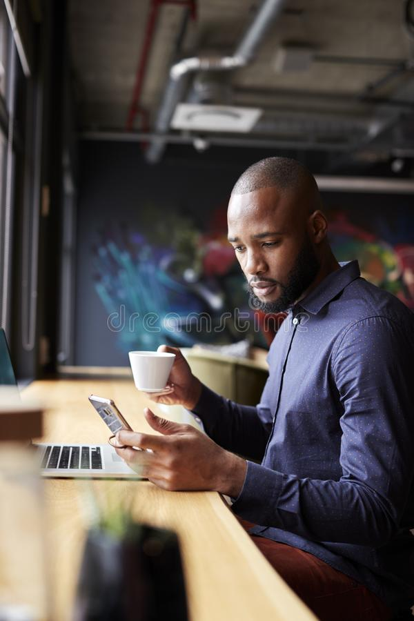 Mid adult black male creative sitting by window having coffee using smartphone, side view, vertical stock images