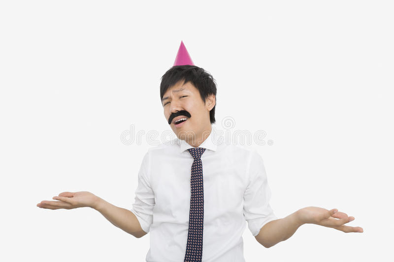 Mid adult businessman shrugging his shoulders over white background stock photo