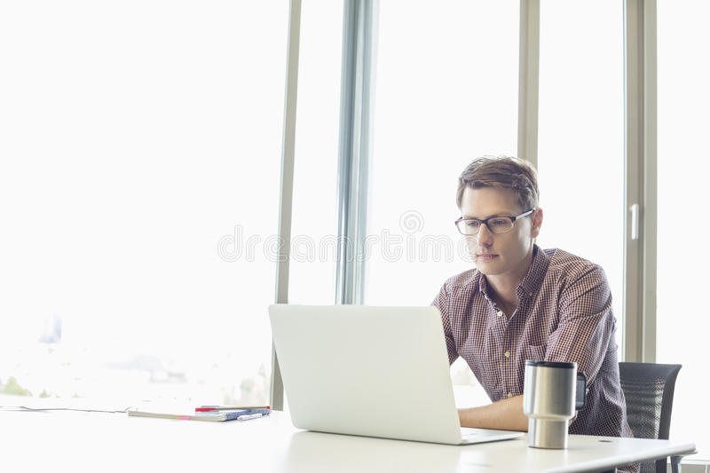Mid-adult businessman using laptop at desk in creative office royalty free stock photography