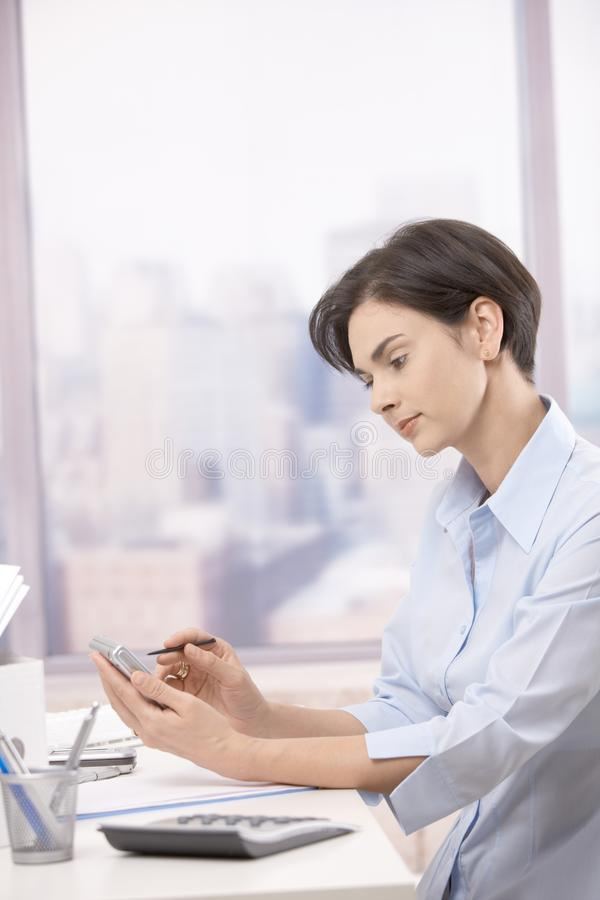Download Mid-adult Businesswoman Using Pda In Office Stock Image - Image of business, daylight: 21446317