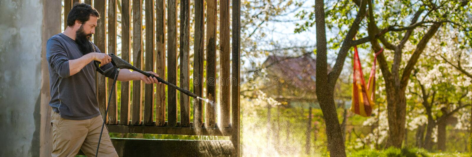 Mid adult caucasian man cleaning a wooden gate with a power washer. High pressure water cleaner used to DIY repair garden gate. stock photos