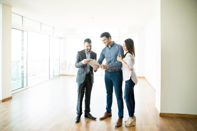 Couple Signing Sale Purchase Agreement By Broker In New Home stock photos