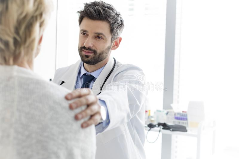 Mid adult doctor consoling mature patient at hospital royalty free stock photo