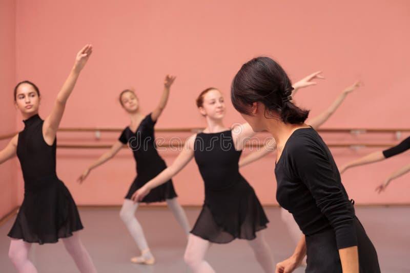Mid adult female ballet teacher instructing medium group of teenage girls. In black dresses. Practicing choreography dancing stock image
