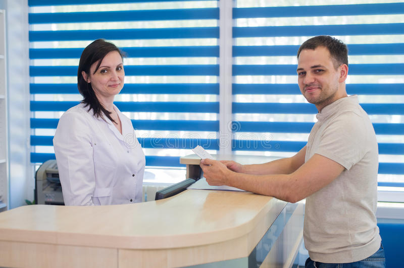Mid adult female receptionist receiving card from patient in dentist clinic.  royalty free stock image