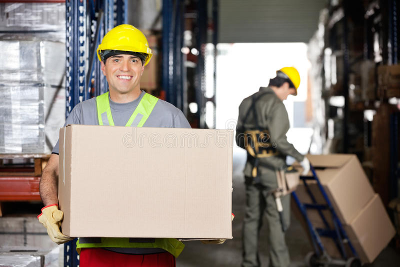 Mid Adult Foreman With Cardboard Box At Warehouse stock images