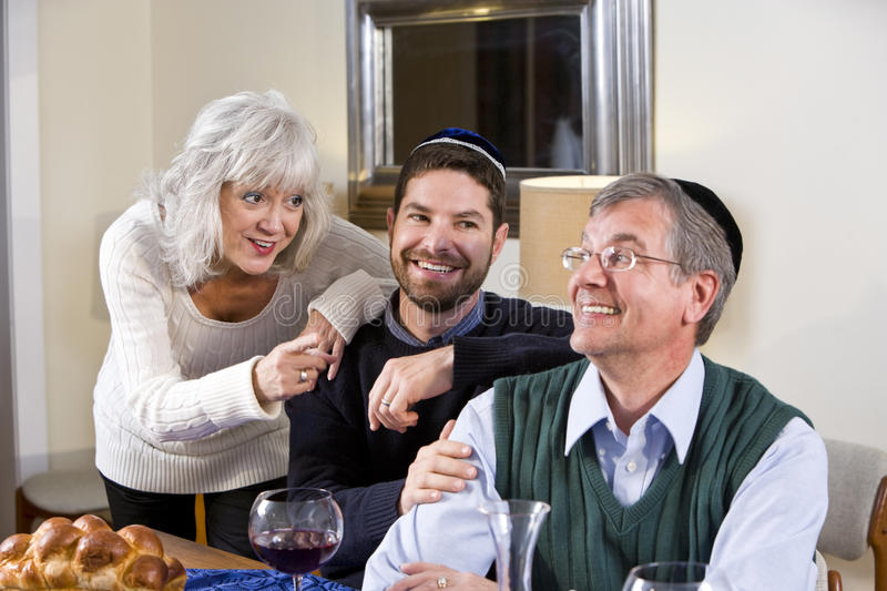 Mid-adult Jewish man at home with senior parents. Mid-adult Jewish man at home smiling with senior parents royalty free stock images