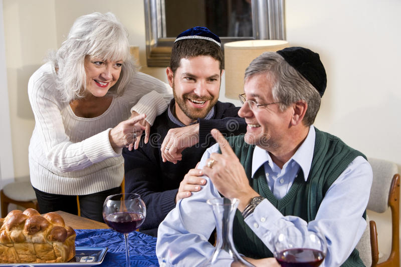 Mid-adult Jewish man at home with senior parents. Mid-adult Jewish man at home smiling with senior parents stock images