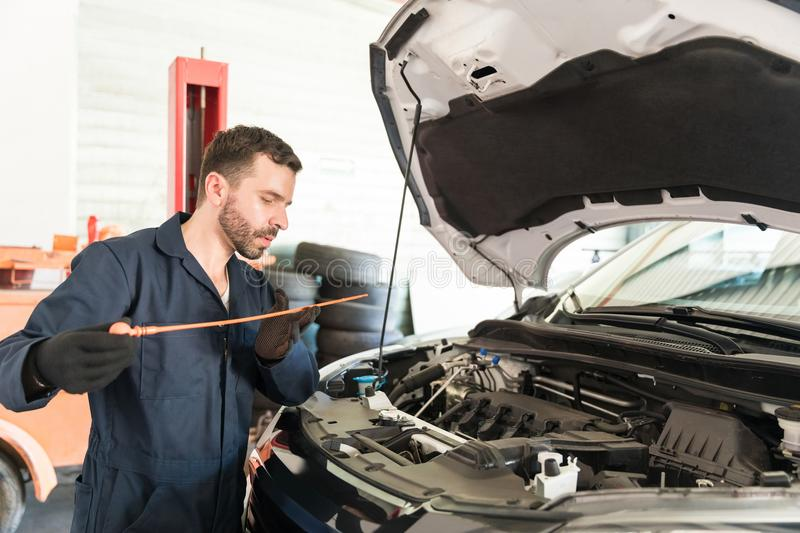 Engineer Checking Oil Level In Car Engine At Workshop royalty free stock images