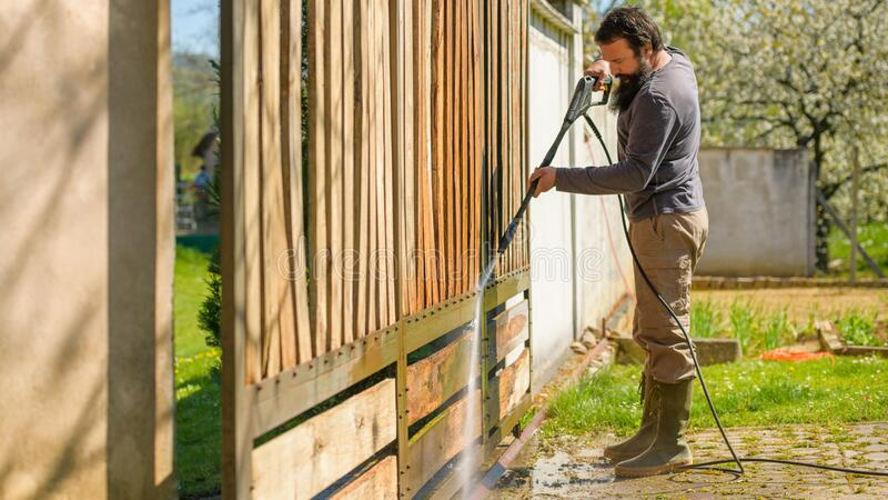 Mid adult man cleaning a wooden gate with a power washer. High pressure water cleaner used to DIY repair garden gate. stock photo