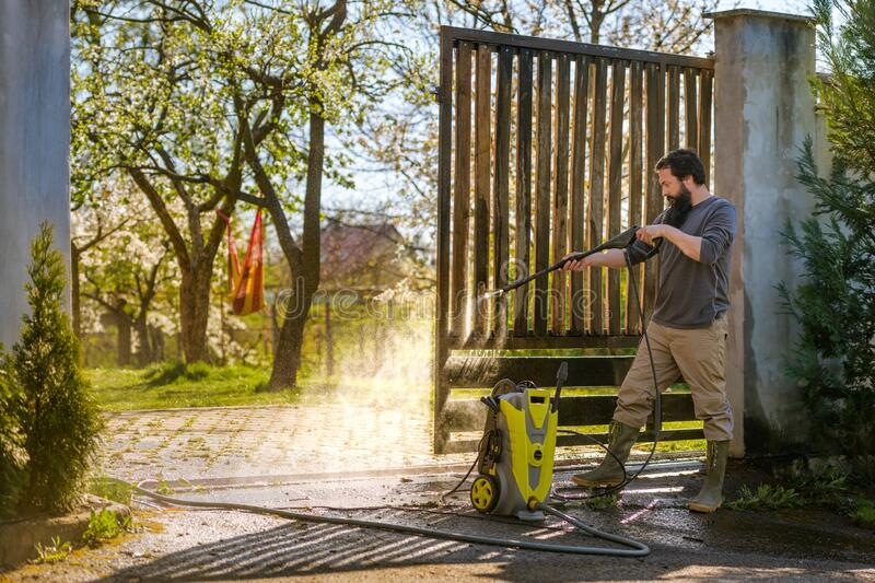 Mid adult man cleaning a wooden gate with a power washer. High pressure water cleaner used to DIY repair garden gate. royalty free stock photos