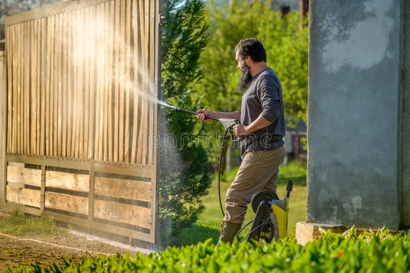 Mid adult man cleaning a wooden gate with a power washer. High pressure water cleaner used to DIY repair garden gate. royalty free stock images