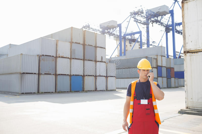 Mid adult man using walkie-talkie in shipping yard royalty free stock photos