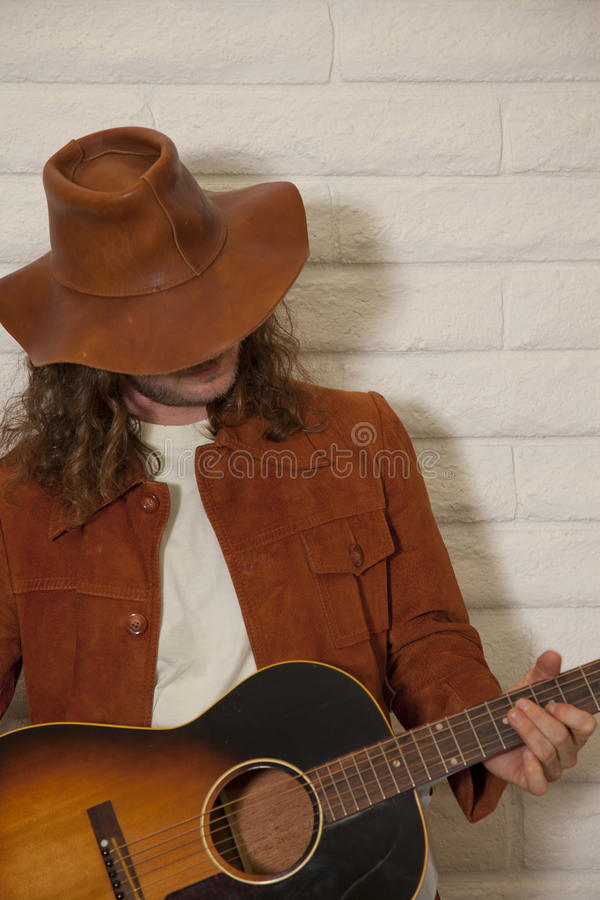 Mid adult man wearing cowboy hat and playing guitar stock photo