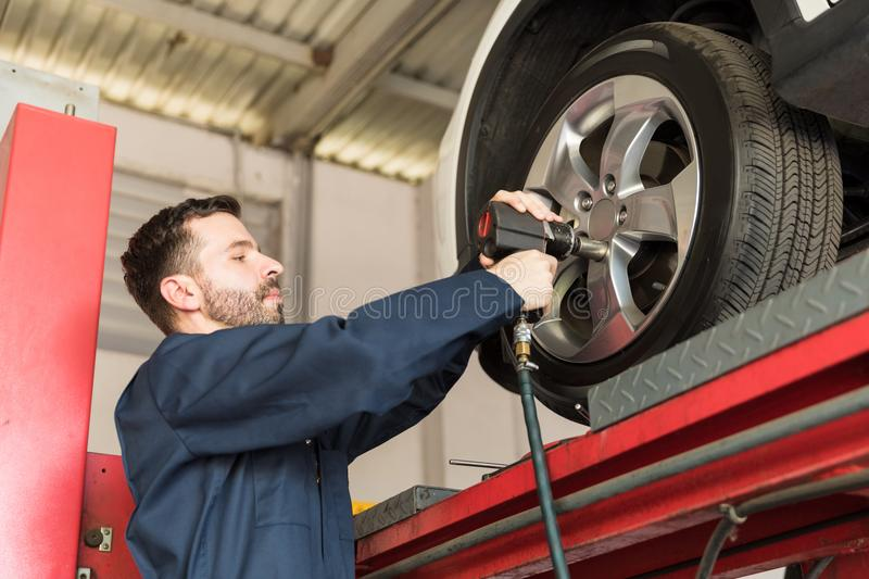 Mechanic Servicing Car Tire With Impact Gun In Garage. Mid adult mechanic servicing car tire with impact gun in garage stock photo