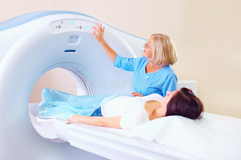 Mid adult medical staff preparing patient to tomography. Mid adult medical staff preparing female patient to tomography royalty free stock photography