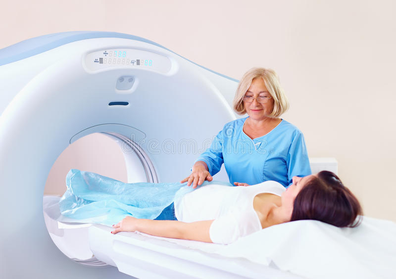 Mid adult medical staff preparing patient to tomography. Mid adult medical staff preparing female patient to tomography stock image